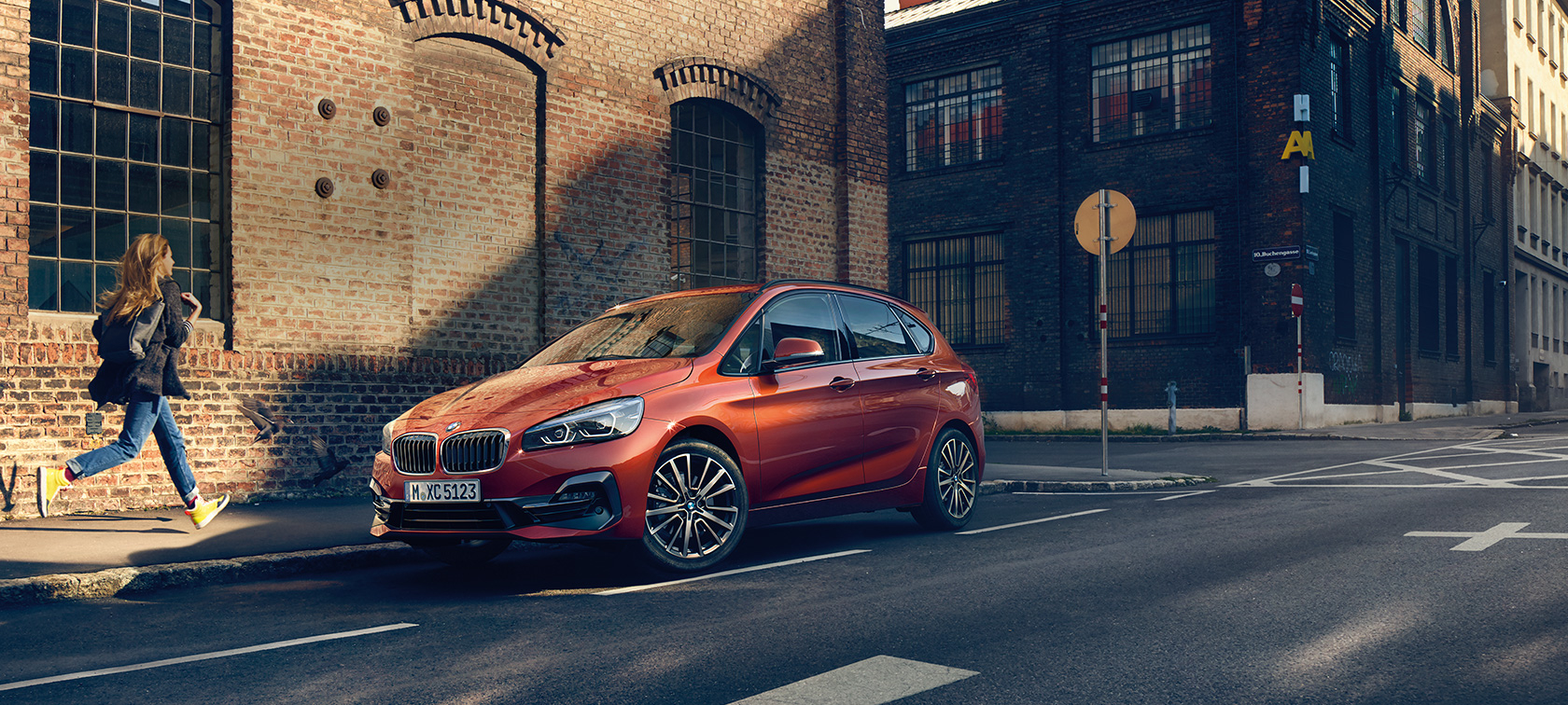 Nuevo BMW Serie 2 Active Tourer F45 2018 Sunset Orange metalizado, vista de tres cuartos frontal, aparcado en la calle